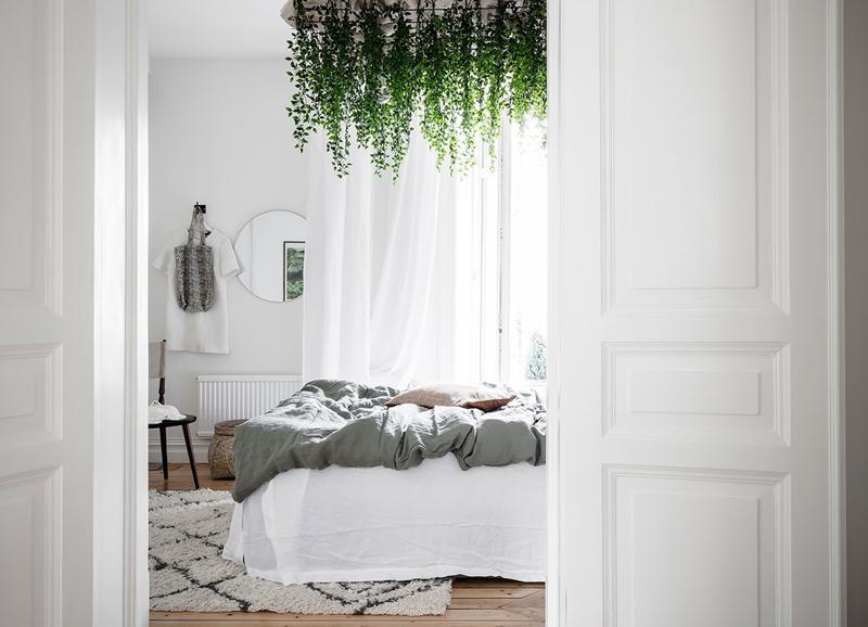 Zien: bijzondere slaapkamer met hangplanten boven het bed